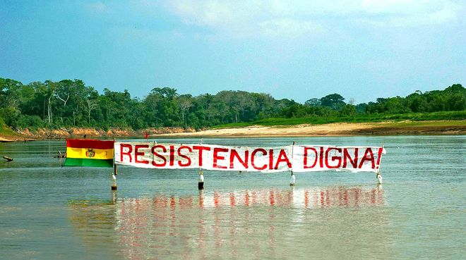 "Protest banner on a river in the Bolivian rainforest: the slogan ""Resistance Means Dignity"" stands next to the Bolivian flag."
