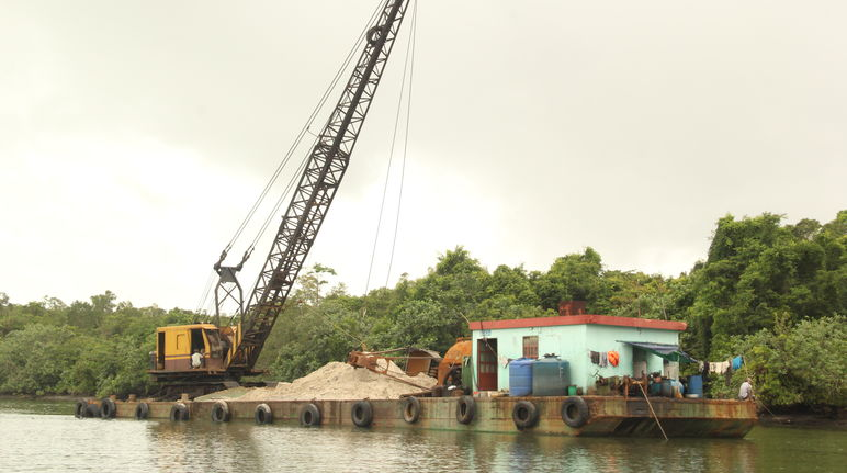 Sand being loaded onto a barge by a dredger