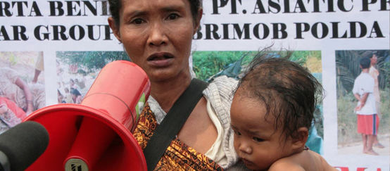 A woman carrying a child and a megaphone