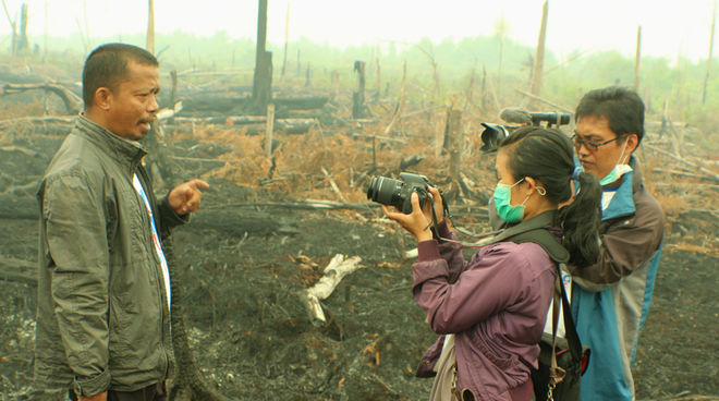 Nordin of Save our Borneo standing on scorched earth, giving an interview