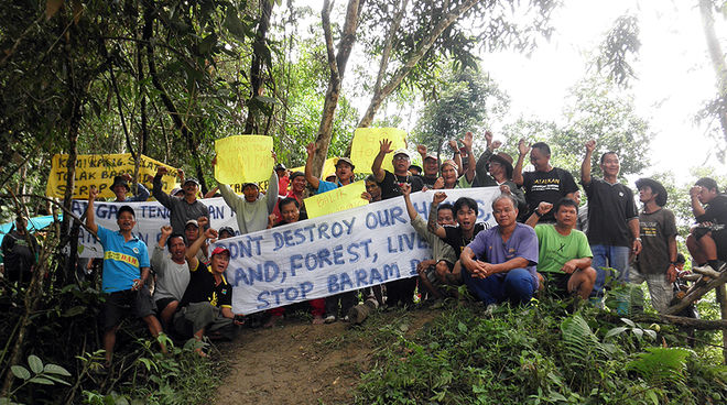 Indigenous peoples of the Sarawak rainforest protesting with banners against Baram Dam