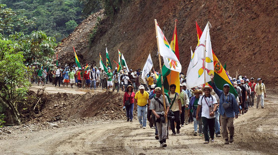 Indians on a protest march with flags in their hands walking up a gravel road