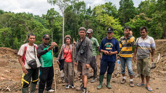 A group of activists and villagers standing together on a clearing