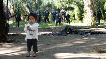 A frightened little girl in front of a group of paramilitaries