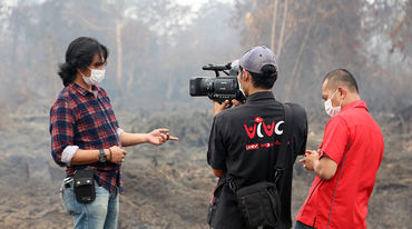 A man being interviewed with a burning rainforest in the background