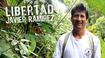 Javier Ramírez standing in front of rainforest plants