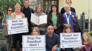People infront of the embassy in Berlin holding protest signs against the dam