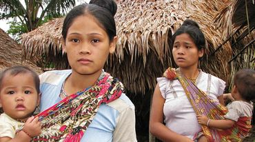 Two indigenous women with their children look worried