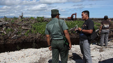 Two men standing infront of a clearance for palm oil palntation
