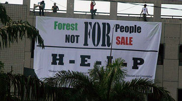 Protesters hanging up a banner: forest for people, not for sale