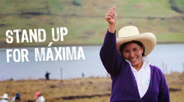 Maxima Acuña smiles and raises her right fist. Other farmers and the Blue Lagoon can be seen in the background.