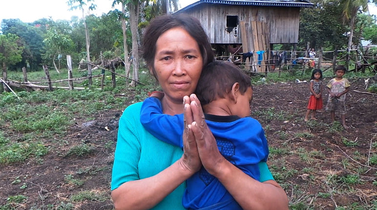 A woman holding a child, standing in front of their makeshift hut after being driven from their land