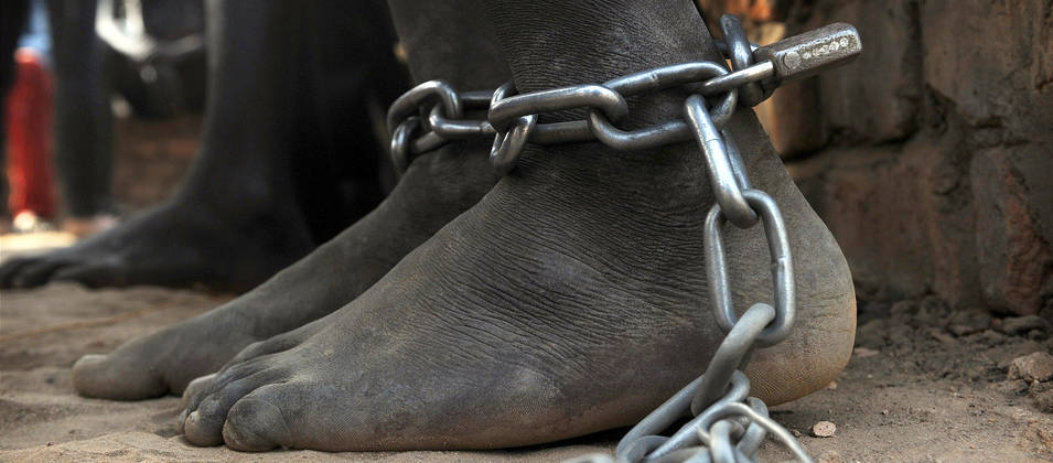 A pair of bare feet bound with chains and a padlock