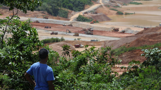 A farmer standing in the forest, looking at an open-pit mine