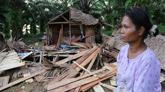 An indigenous woman stands in shock in front of her demolished house