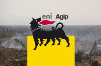 An Eni logo in front of the burning remains of a rainforest