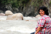 Environmental activist Berta Cáceres sitting on a rock by a river, looking over her shoulder to the camera